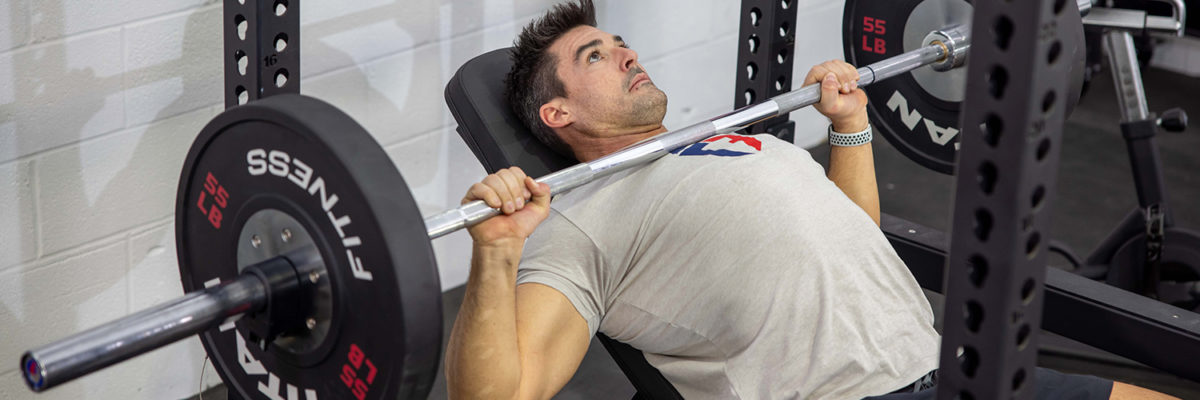 Male on an workout incline bench inside of a squat rack. He is lifting 135 pounds in weight